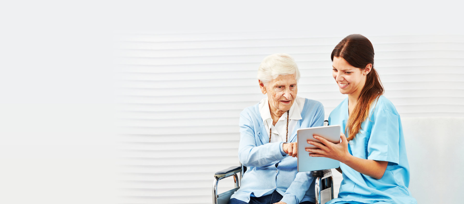 caregiver and senior woman reading on a table